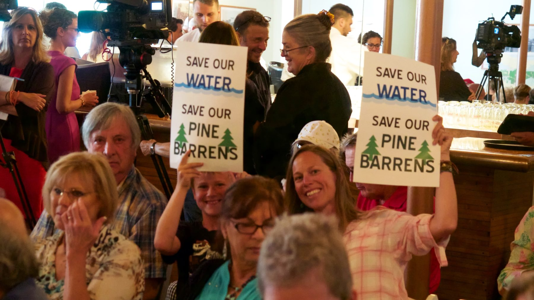 People holding signs that read save our water save our pine barrens