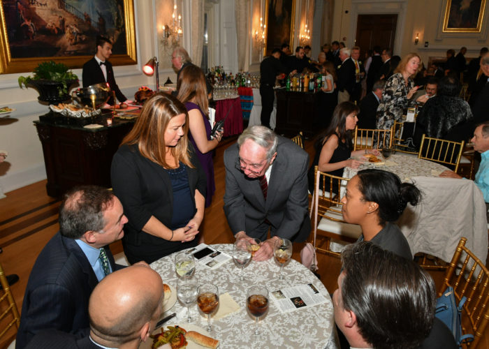 People gathered around a table at the cocktail hour of the gala
