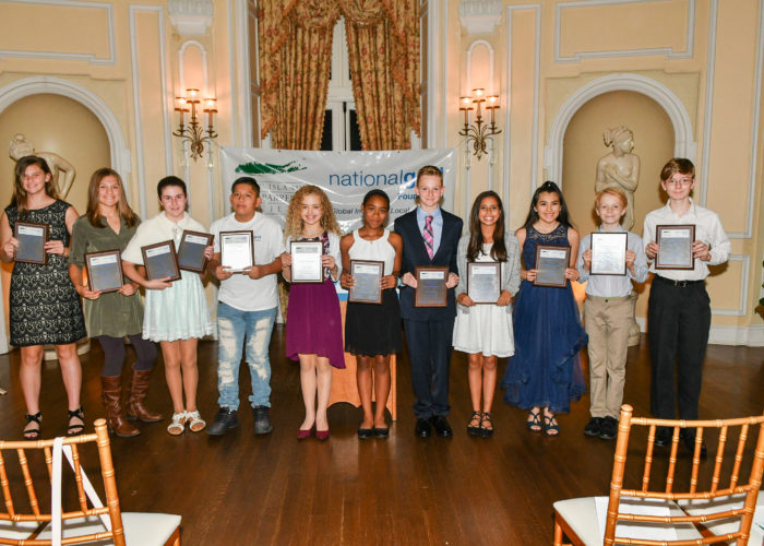 A group of middle school students show off their awards