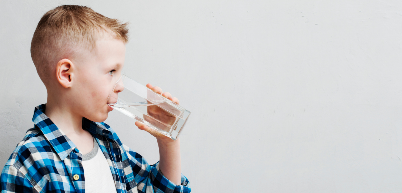 Little boy drinking water out of a glass