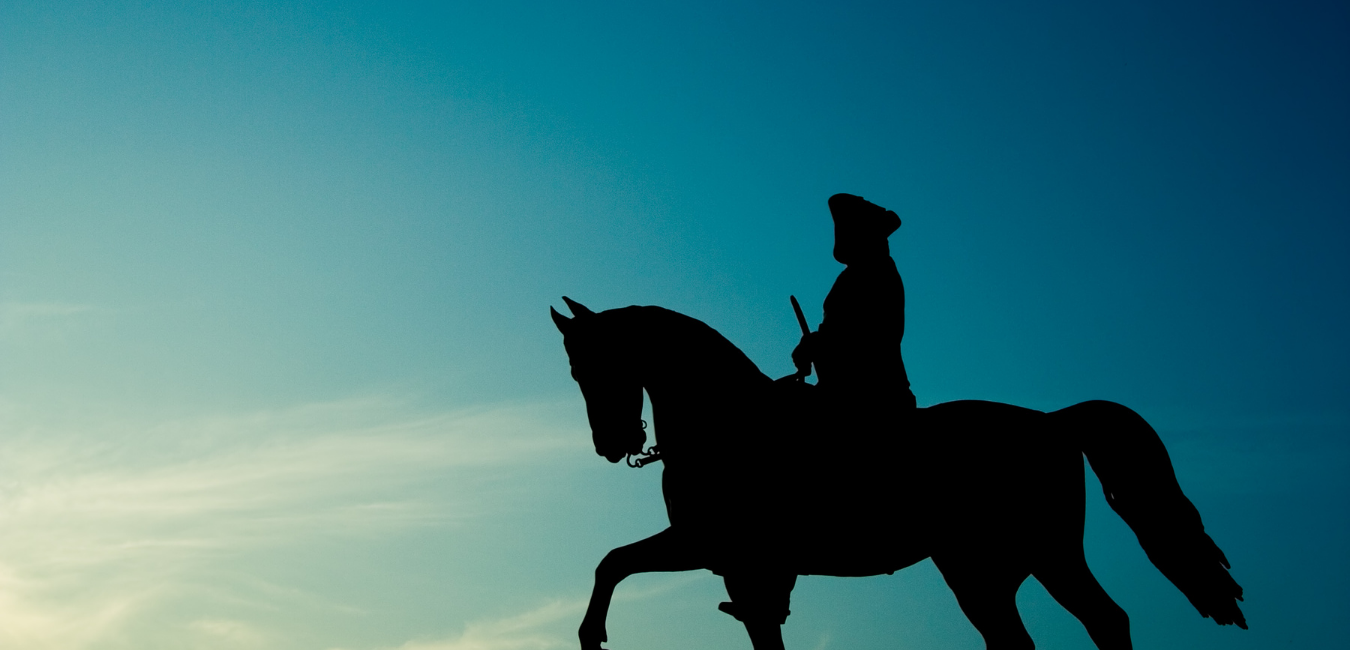 George Washington silhouetted on a horse with a blue sky backdrop