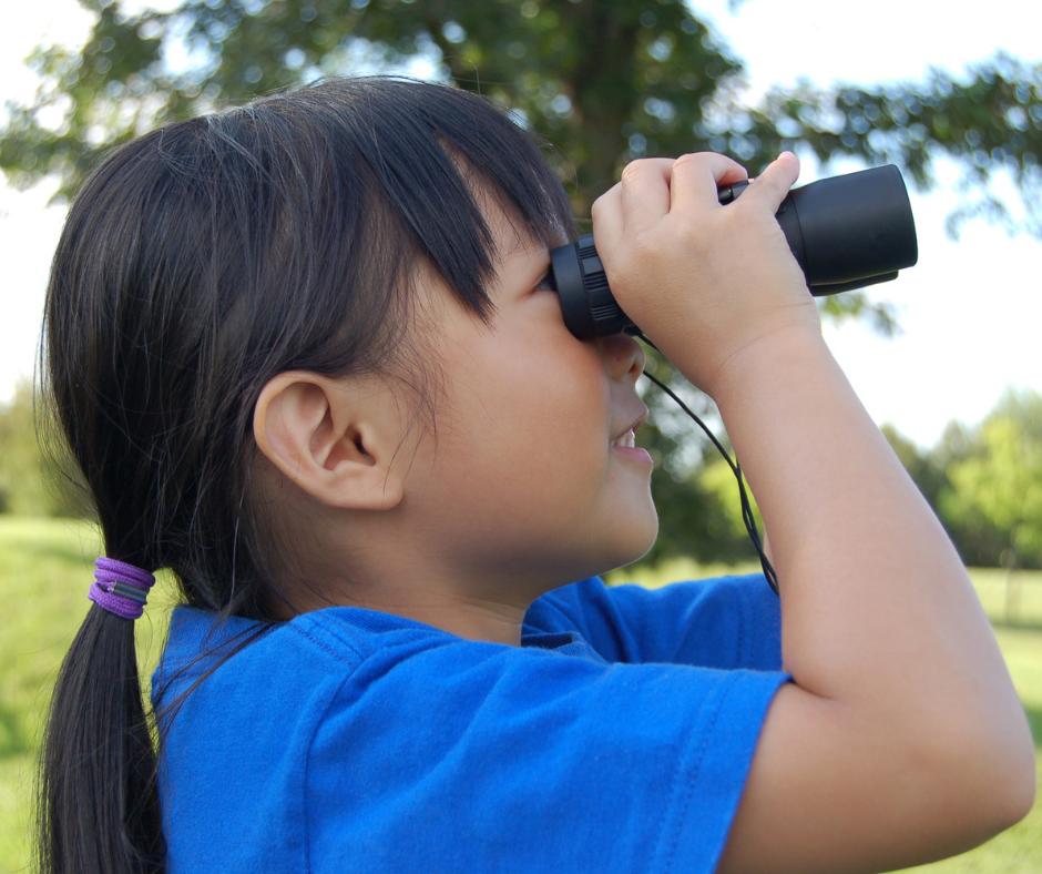 Little girl looking through binoculars looking for birds