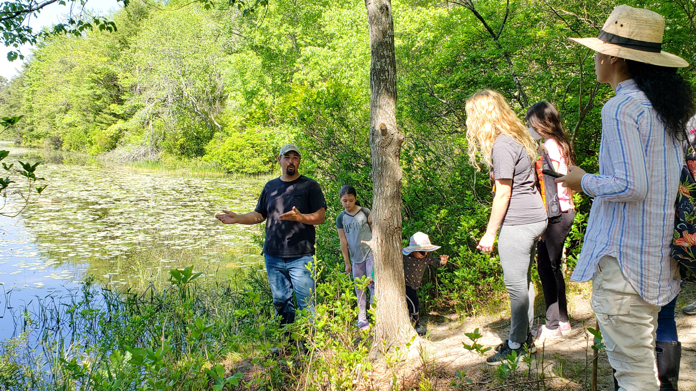 Pine Barrens educator leading a group hike of people around a pond